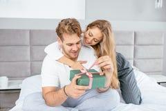 Красивая жена помогая раскрыть подарочную коробку к ее красивому счастливому супругу стоковая фотография rf