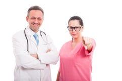 Красивая женская медсестра около доктора указывая на вас Стоковое Изображение RF