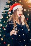 Красивая женская модельная шляпа santa носки Выпивая шампанское и еда клубник около рождественской елки стоковые изображения
