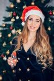 Красивая женская модель носит шляпу santa со стеклом шампанского Портрет девушки в черном платье, конец вверх стоковые изображения rf