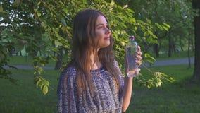 Красивая женская питьевая вода hiker в лесе на заходе солнца Девушка в платье выпивает холодную воду от пластичной бутылки сток-видео