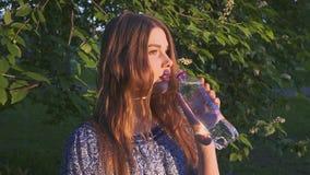 Красивая женская питьевая вода hiker в лесе на заходе солнца Девушка в платье выпивает холодную воду от пластичной бутылки видеоматериал