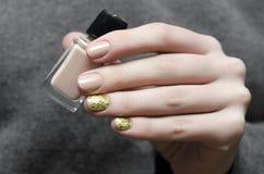 Красивая женская рука с бежевым дизайном ногтя Стоковые Изображения