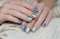 Красивая женская рука с голубым и зеленым дизайном ногтя яркого блеска Стоковая Фотография RF