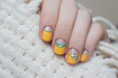 Красивая женская рука с желтым дизайном ногтя Стоковые Фотографии RF