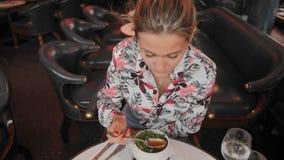 Красивая женская француженка в variegated рубашке ест традиционный французский луковый суп с гренками и зеленые цвета в a акции видеоматериалы