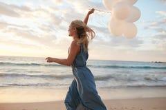 Красивая женщина бежать на пляже с воздушными шарами Стоковые Фото