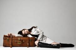 Красивая женщина битника брюнет в серой куртке осени лежа на кожаной коричневой ретро сумке перемещения на сером цвете стоковое изображение rf