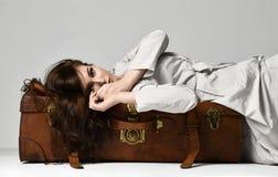 Красивая женщина битника брюнет в серой куртке осени лежа на кожаной коричневой ретро сумке перемещения на сером цвете стоковая фотография rf