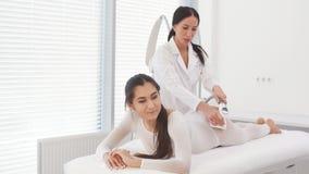 Красивая женщина брюнета получая массаж LPG для поднимаясь тела в костюме LPG акции видеоматериалы