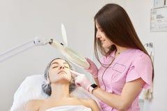 Красивая женщина брюнета проходя медицинский осмотр, рассматриваемый cosmetologist перед иметь впрыску botox beatitude стоковое изображение