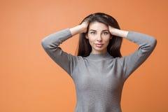 Красивая женщина брюнета с длинными волосами изолированными на оранжевой предпосылке стоковые изображения rf