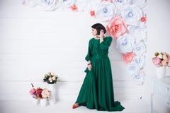 красивая женщина брюнет в silk зеленом платье представляя с цветками на светлой предпосылке стоковые фотографии rf