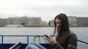 Красивая женщина брюнет использует ее smartphone сидя в шине реки, отдыхая Она радостно усмехается st petersburg России акции видеоматериалы