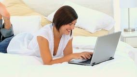 Красивая женщина брюнет наслаждаясь болтовней на ее компьтер-книжке видеоматериал