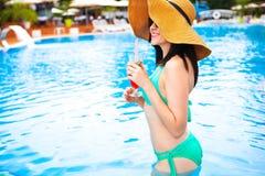 Красивая женщина брюнет нося шляпу и солнечные очки, наслаждаясь Стоковая Фотография