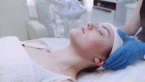 Красивая женщина брюнет получая профессиональную лицевую обработку с паром в курорте красоты в замедленном движении естественно видеоматериал