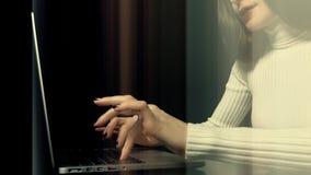 Красивая женщина брюнет работая на ее компьтер-книжке против черной предпосылки Абстрактные светлые вертикальные линии через рамк Стоковые Фотографии RF