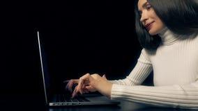 Красивая женщина брюнет работая на ее компьтер-книжке против черной предпосылки Стоковая Фотография