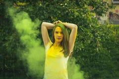 Красивая женщина брюнет с взрывать зеленый сухой порошок Стоковые Фото