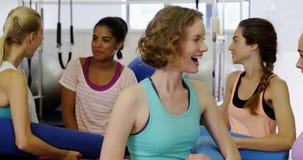 Красивая женщина взаимодействуя друг с другом в студии фитнеса акции видеоматериалы