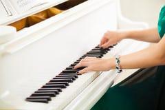 Красивая женщина вручает играть музыку на белом рояле стоковые изображения rf