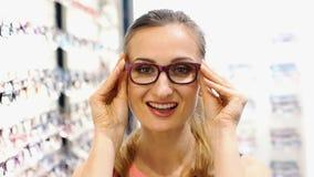 Красивая женщина выбирая новые стекла в магазине акции видеоматериалы