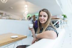 Красивая женщина выпивает кофе в современном кафе с белым интерьером и улыбками помадка чашки круасанта кофе пролома предпосылки Стоковое Изображение