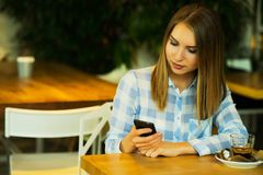 Красивая женщина выпивает кофе и читает новости утра Стоковое Изображение RF