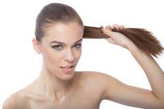 Красивая женщина вытягивая ее волосы, над белым backgroung Стоковое Изображение