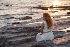 Красивая женщина в белом платье наслаждаясь заходом солнца Стоковая Фотография RF