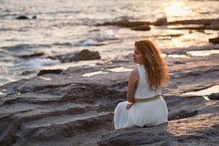 Красивая женщина в белом платье наслаждаясь заходом солнца Стоковое Изображение