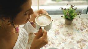 Красивая женщина в белой блузке, выпивая кофе в ресторане сток-видео