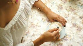 Красивая женщина в белой блузке, выпивая кофе в ресторане видеоматериал