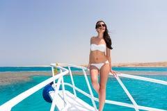 Красивая женщина в белом купальнике стоя на носе y Стоковое фото RF