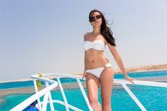 Красивая женщина в белом купальнике стоя на носе ya Стоковые Изображения
