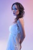 Красивая женщина в белом платье и голубом свете изолированных на голубой предпосылке Стоковое Изображение