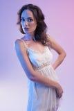 Красивая женщина в белом платье и голубом свете на голубой предпосылке Стоковые Изображения RF