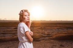 Красивая женщина в белом платье представляя на заходе солнца с сексуальным взглядом стоковые фото
