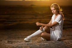 Красивая женщина в белом платье представляя на заходе солнца с сексуальным взглядом стоковая фотография rf