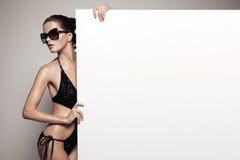 Красивая женщина в бикини держа большую пустую белую афишу стоковая фотография rf