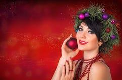 Красивая женщина в венке ветвей рождественской елки и новый Стоковые Изображения