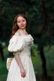 Красивая женщина в винтажном беже платья Милая девушка в длинном платье идя в сосновый лес стиль ферзя, принцессы Стоковое фото RF