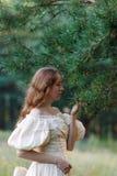 Красивая женщина в винтажном беже платья Милая девушка в длинном платье идя в сосновый лес стиль ферзя Стоковые Изображения RF