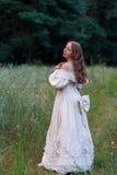 Красивая женщина в винтажном беже платья Милая девушка в длинном платье идя в сосновый лес стиль ферзя Стоковые Изображения