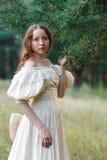 Красивая женщина в винтажном беже платья Милая девушка в длинном платье идя в сосновый лес стиль ферзя Стоковые Фотографии RF