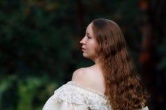 Красивая женщина в винтажном беже платья Милая девушка в длинном платье идя в сосновый лес стиль ферзя Стоковое Фото