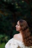 Красивая женщина в винтажном беже платья Милый портрет девушки в длинном платье идя в сосновый лес стиль ферзя, принцев Стоковые Фото
