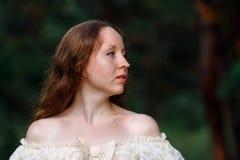 Красивая женщина в винтажном беже платья Милый портрет девушки в длинном платье идя в сосновый лес стиль ферзя Стоковое фото RF
