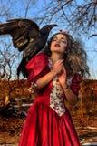 Красивая женщина в винтажном красном платье с чернотой стоковое изображение